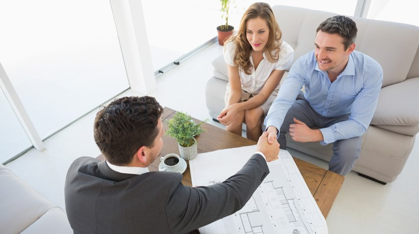 Young buyers with real estate agent in handshake
