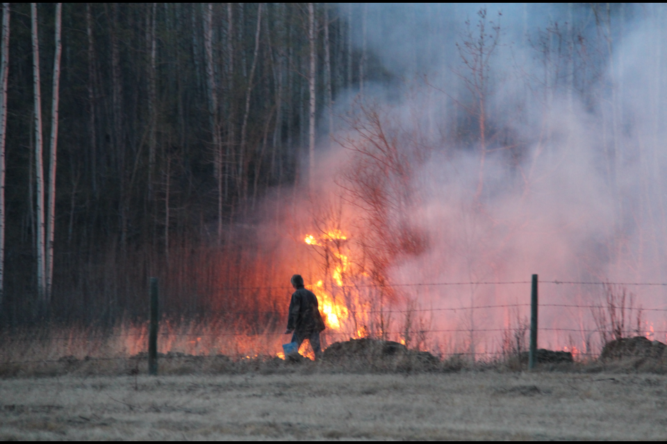 Dave Abel walks along a fire line west of Dawson Creek. Strong winds and dry conditions whipped up dozens of fires across the region, prompting multiple evacuation orders across the Peace.