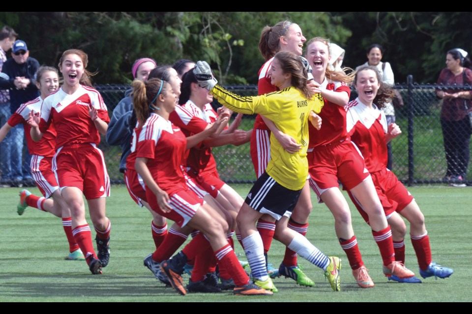 Richmond Ravens goalkeeper Ali Burns is mobbed by her teammates after making the clinching save in her team's 1-0 win in penalty kicks over Surrey in the Coastal Cup semi-finals.