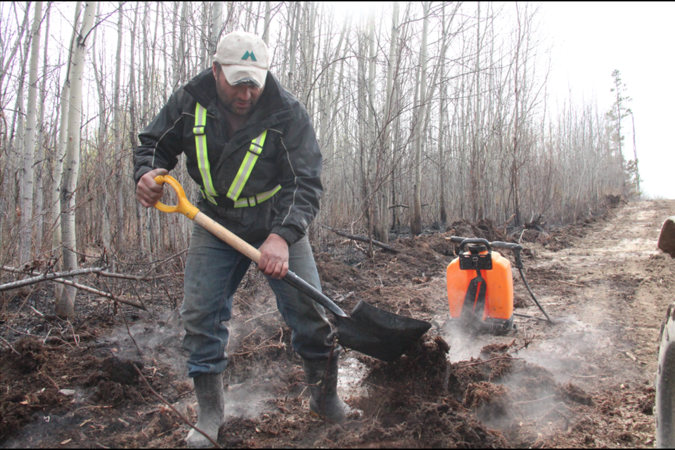 Travis Nelson turns over a smoking pile of dirt near his home in Arras. A wildfire sparked April 18 burned nearly 400 hectares in the community.