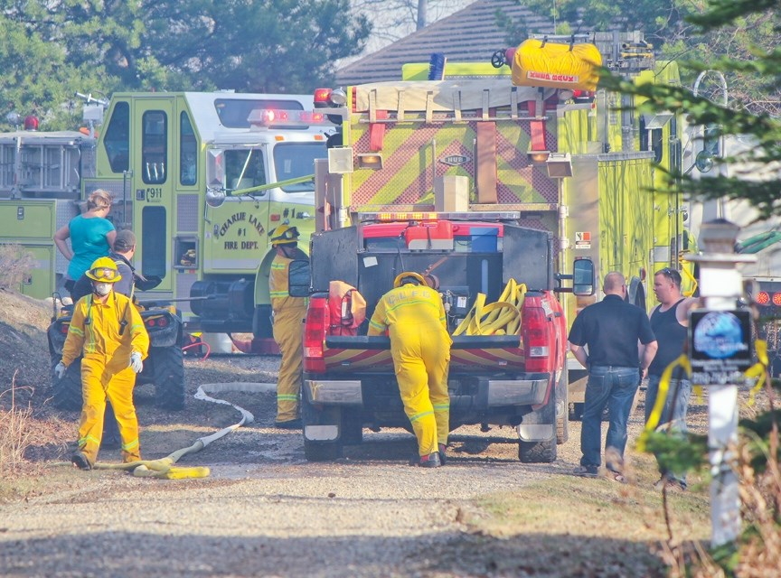 Charlie lake firefighters work to contain a fire just below Ken and Darby Forest's home on Brown Road on Monday, April 18.