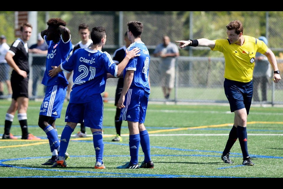 I see you: EDC Burnaby's Joel Padmore (far left, in blue) and teammates Daniel Morello and Felipe Viera react after Padmore's penalty kick was called back by referee Scott Milliquet due to a foot being inside the 18-yard box. Morello would retake the kick and score as they won their quarterfinal game at Burnaby Lake West.