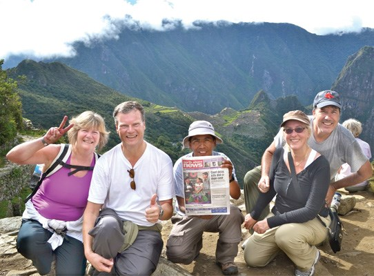 Susan and Peter Kvarnstrom, and Arlene and Dale Peniuk, take the North Shore News to the site of the Sun Gate, with help from their guide Edson (centre), while on a visit to Peru. Machu Picchu is in the background.