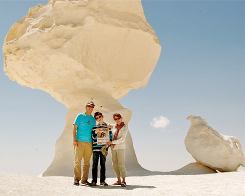Michael Sharp, Alex Sharp and Caroline Helbig stop in the shade of an amazing rock formation in Egypt's White Desert.