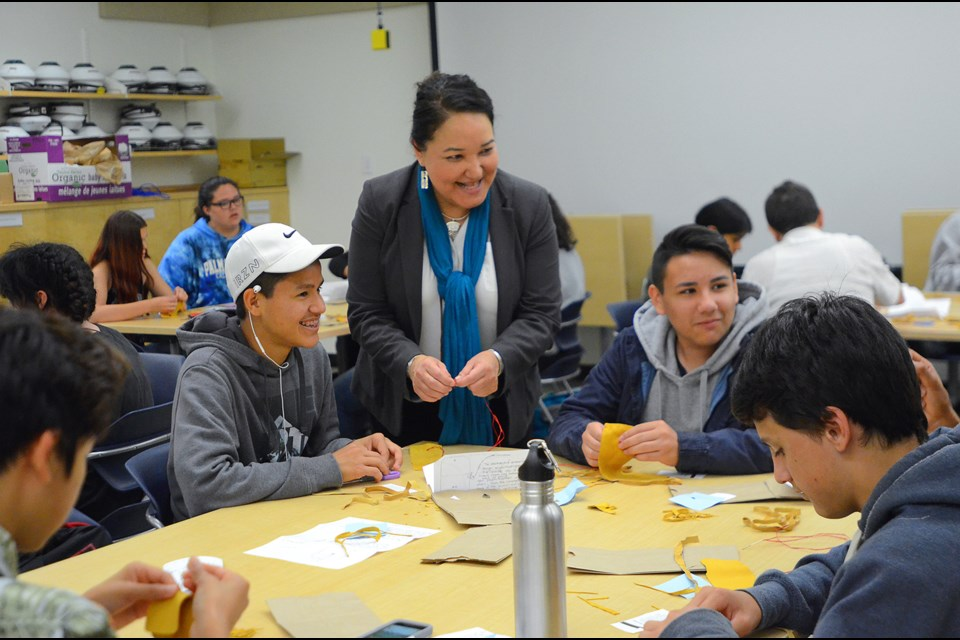 Marcia Guno, director of SFU's Indigenous Student Centre helps a group of high school students at the university's Academic Summer Camp for Aboriginal Students make medicine bags.