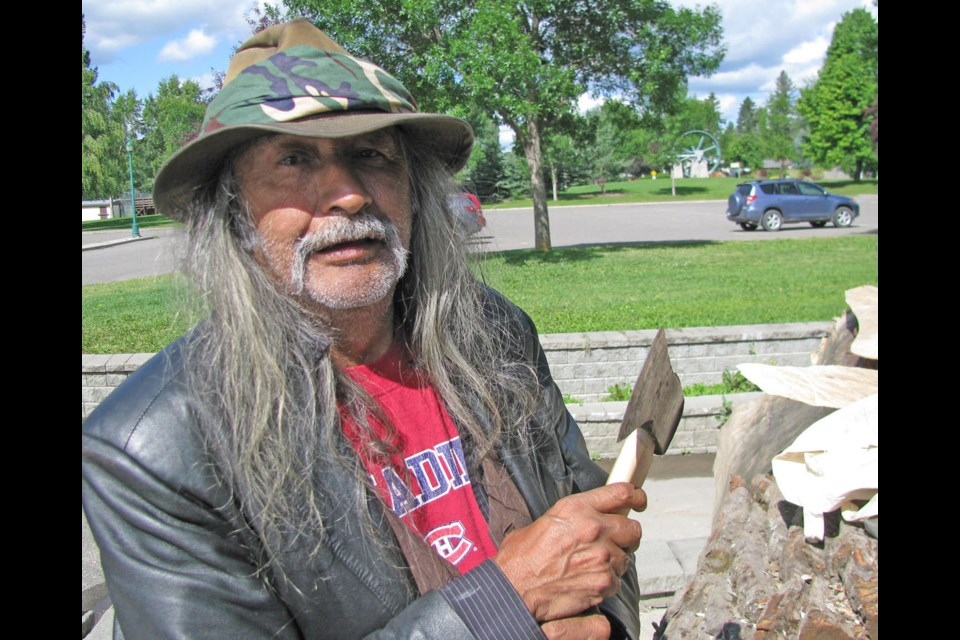 Robert Frederick talks about his ax as he prepares to work on the dugout canoe that will become part of the exhibit at The Exploration Place called The Path of Our Paddle.