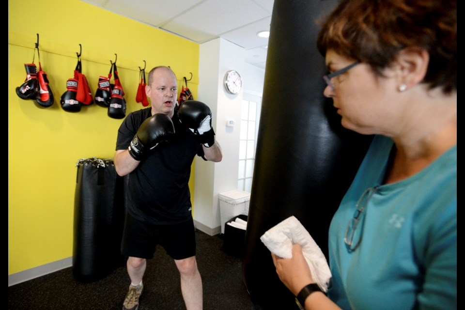 Amy van Weelderen steadies the punching bag as her husband Floris trains at a Rock Steady Boxing class in Vancouver.