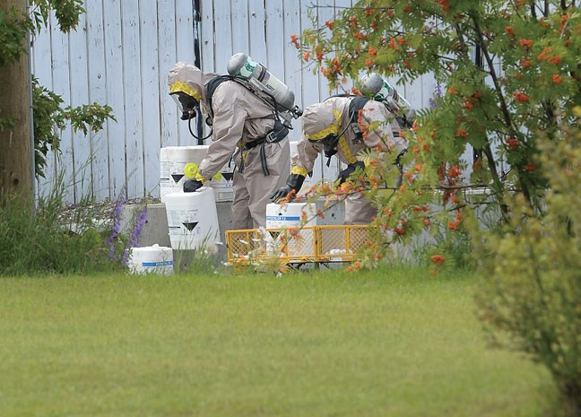 City of Prince George Fire/Rescue Service hazmat team heads in to deal with containers of hazerdous materials found in an alley of of 13th Avenue behind Central Street Tuesday. Citizen photo by Brent Braaten July 19 2016
