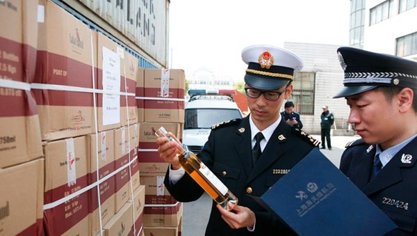 Chinese customs officials are seen inspecting and documenting seized boxes of Lulu Island WInery wine. Photo sourced from XinMin.com