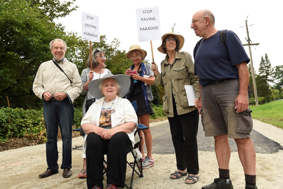 Mark Battersby (left) and a handful of other protesters, including Diana Davidson (centre) demonstrated against the use of asphalt on Arbutus Greenway earlier this week. photo Dan Toulgoet