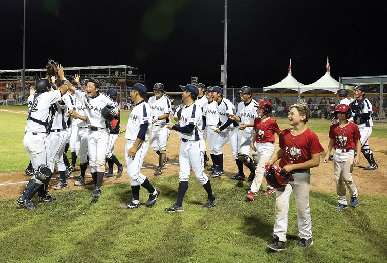 Players from Team Japan celebrate after defeating the Roswell Invaders in the gold-medal game of the Ramada World Baseball Challenge. Citizen Photo by James Doyle August 20, 2016