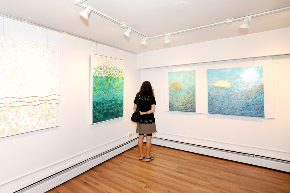 A visitor examines the work at the Diffusion opening reception.