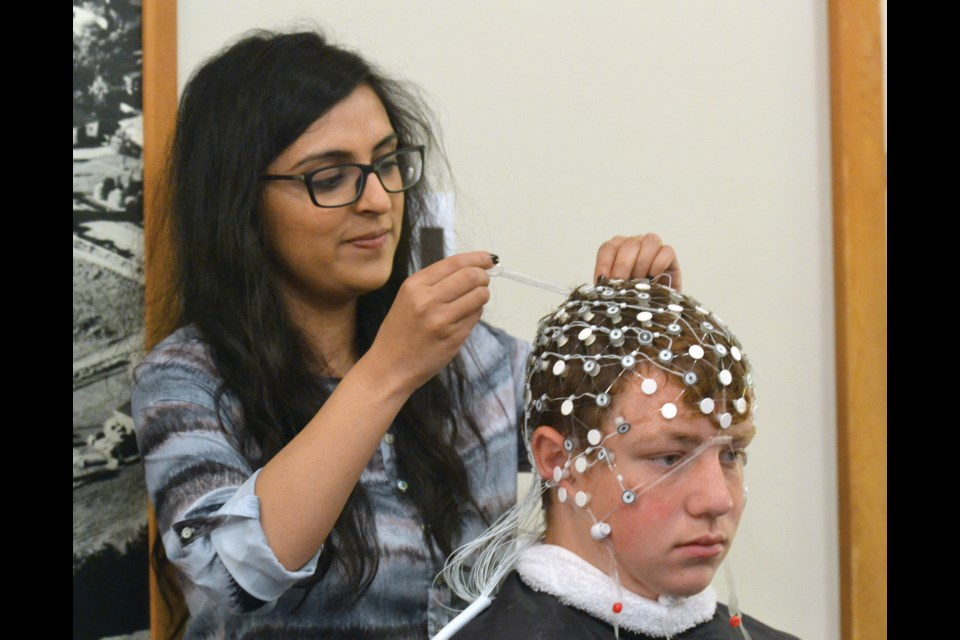 Amna Hyder prepares Richmond FC player Blake Charlesworth for an EEG scan as part of the club's baseline testing session last weekend at Brighouse Park. The youth soccer association has teamed up with UBC for the leading edge project.