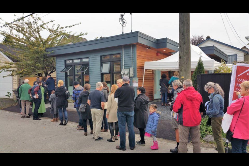 Attendees at this year's Vancouver Heritage Foundation's laneway house tour lined up to view a small single-level house. Photo Michael Geller