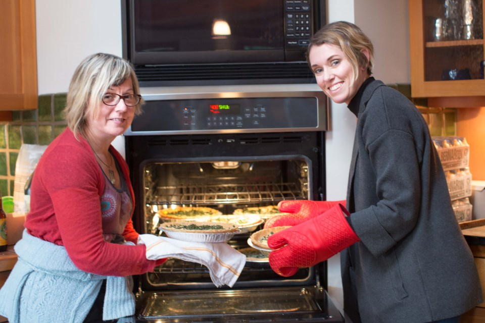Leah May Walker of Bowen Agricultural Alliance (left) and Michelle Catherine Nelson, author of The Urban Homesteading Cookbook (right) pull fragrant walnut, yam, blue cheese and seaweed quiches from the oven, foraged and prepared by the group of Bowen Islanders participating in the workshop and long table lunch last Saturday.