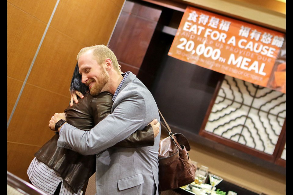 Elaine Cheng, whose family owns Fortune House Seafood Restaurant in Burnaby, and Derek Juno of Mealshare embrace during a celebration last month in honour of Fortune House's commitment to Mealshare, a Vancouver-based charity that helps feed kids in need locally and abroad.