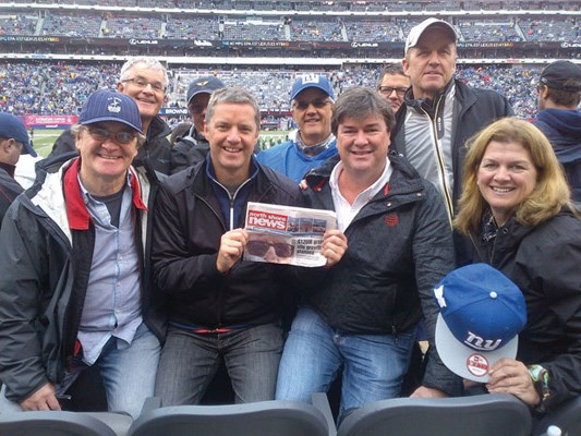 John O'Neill (holding the paper) celebrates his 50th birthday at a New York Giants home game with his six brothers and two in-laws.