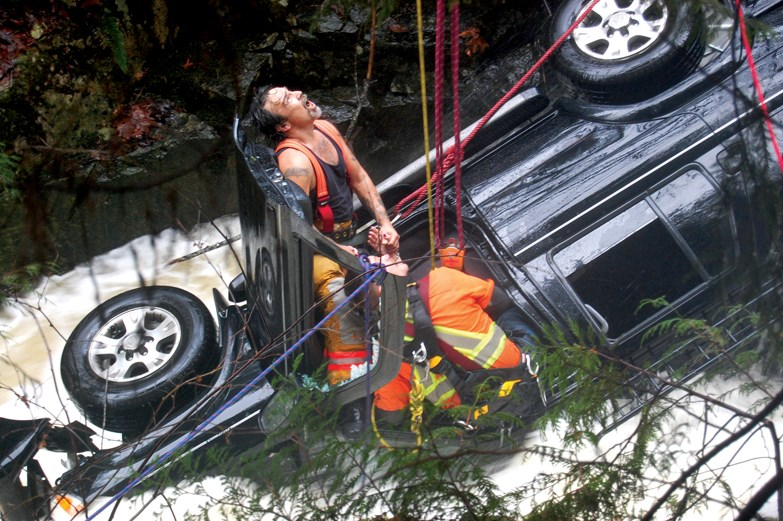 Firefighters Bill Gilkes (left) and Tyrel Brackett perform a high angle rescue to free a Surrey woman trapped after her SUV plunged into a creek near Middlepoint on Nov. 23.