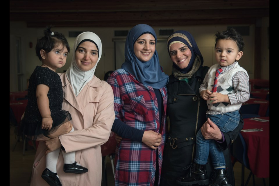 From left to right, Manar Alsaid Ahmed with daughter Salma, Leena Al Ahmad and Asmaa Qawas with son Motaz, were just some of the Syrian refugees who hosted Saturday's community dinner at the Mount Pleasant Neighbourhood House as a way of showing their appreciation to Canadians. Photo Rebecca Blissett