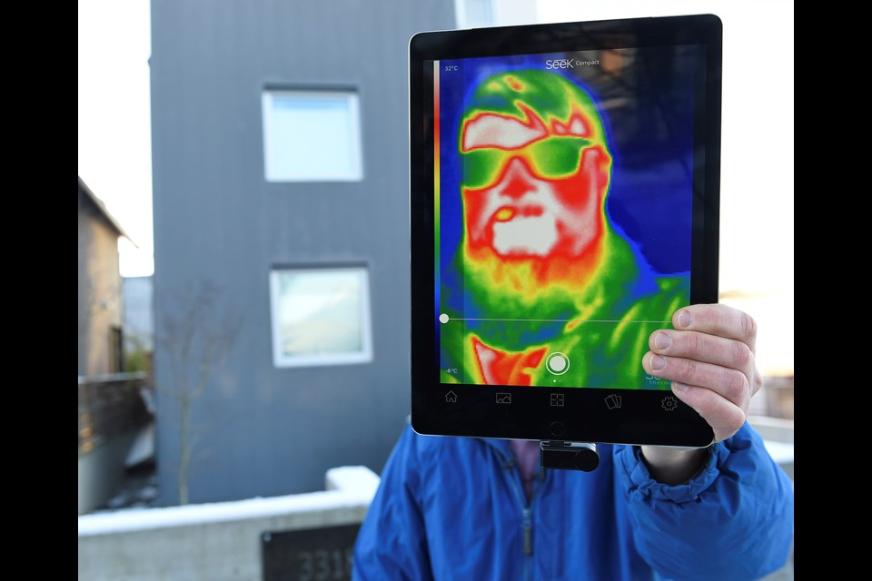 Chris Higgins, a green building planner for the City of Vancouver, demonstrates how a thermal imaging camera works. Photo Dan Toulgoet