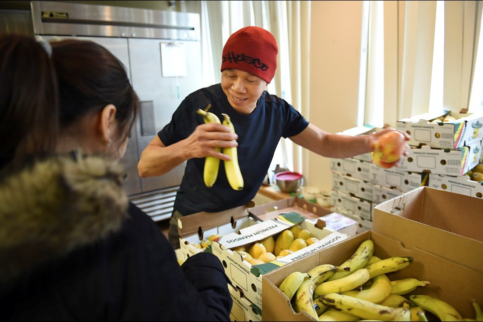 A volunteer hands out fresh fruit at Strathcona Community Centre Jan. 27, 2017. The free weekly food program is at risk if the community centre can't secure funding for the program's co-ordinator. Photo Dan Toulgoet