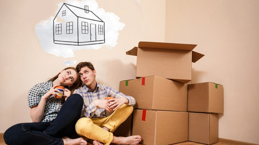 Young couple first time home buyers dreaming with boxes