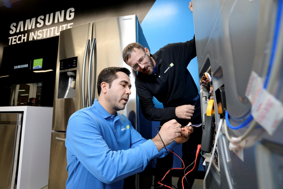 Vancouver Community College student Reza Golshane and Samsung Tech Institute instructor Noel Vanderveer work on a fridge at the institute's unveiling Feb. 23. Photo Jennifer Gauthier