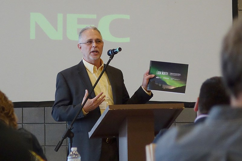 Dr. William Ashton of Brandon University's Rural Development Institute holds up a copy of the Look North Indigenous Economy Report April 10 in Thompson.