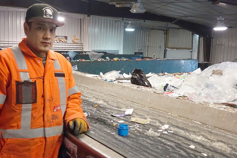 Thompson Recycle Centre employee Aaron Carriere stand by the residential recycling sorting line with
