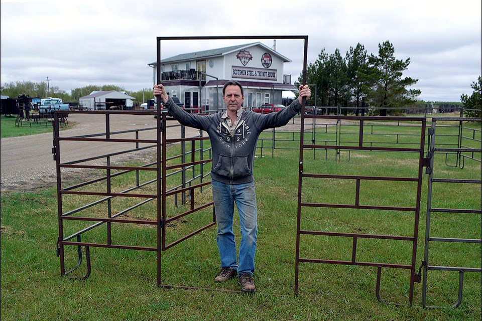 Dean Munchinsky, owner of Scotsmum Steel & The Nut House, stands amongst custom made corral panels on the company's lot.