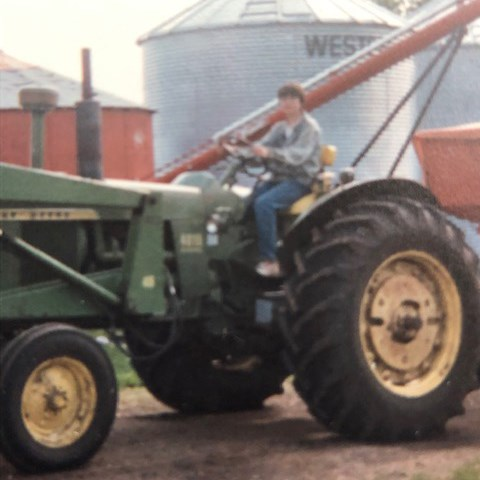 Carla Antichow driving a tractor while growing up on her family's farm.