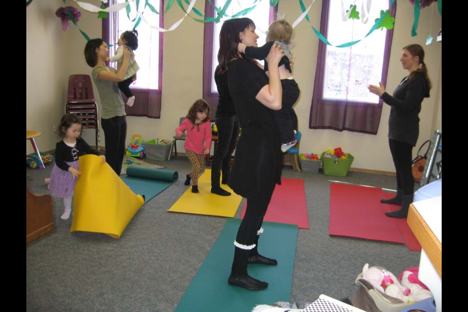 Leanne Popoff from Admyred Yoga & Wellness Studio was teaching yoga to parents of newborns and children up to 18 months of age. Gillian Rice with her son Lowell Rice is in front, while to the left is Masako Knight and her daughters Emma and Maya Knight.