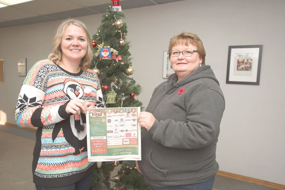 From left, Estevan Mercury Publications sales manager Deanna Tarnes holds up a copy of the Estevan Mercury Bingo poster contest with grand prize winner Brenda Turnbull.