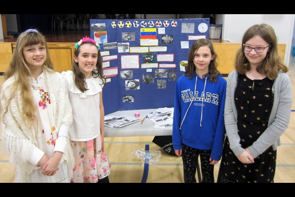 Becky Klop, Abby Calvin, Leah Fraser and Mikayla Gonder with their display on Venezuela.