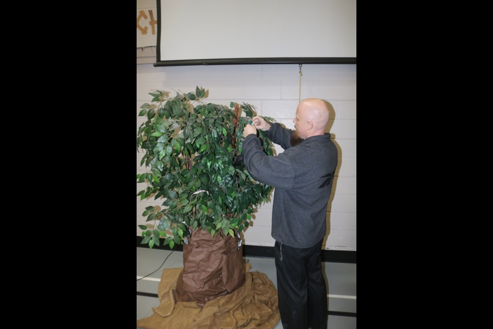 St. Paul's School teacher Mike Laskowski ties a wish ribbon to the Wishtree at the launch of the One Community, One Book, program Monday.