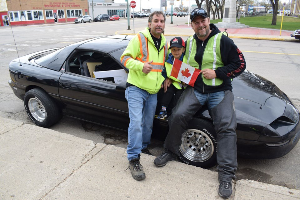 Jay Riedel, left, and Pat King, right, pictured here with Riedel's great-nephew Kaiden Curtis, were in Estevan Saturday for the Yellow Vest protest.