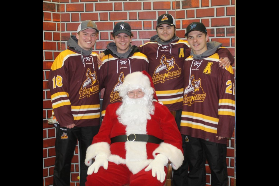 Outback Thunder players Tyrell Nicklen, Tristin Strunk, Brett Harper, David Wiens pose with Santa Claus, who appeared at the Carrot River United Church during the festivities. Photo by Jessica R. Durling