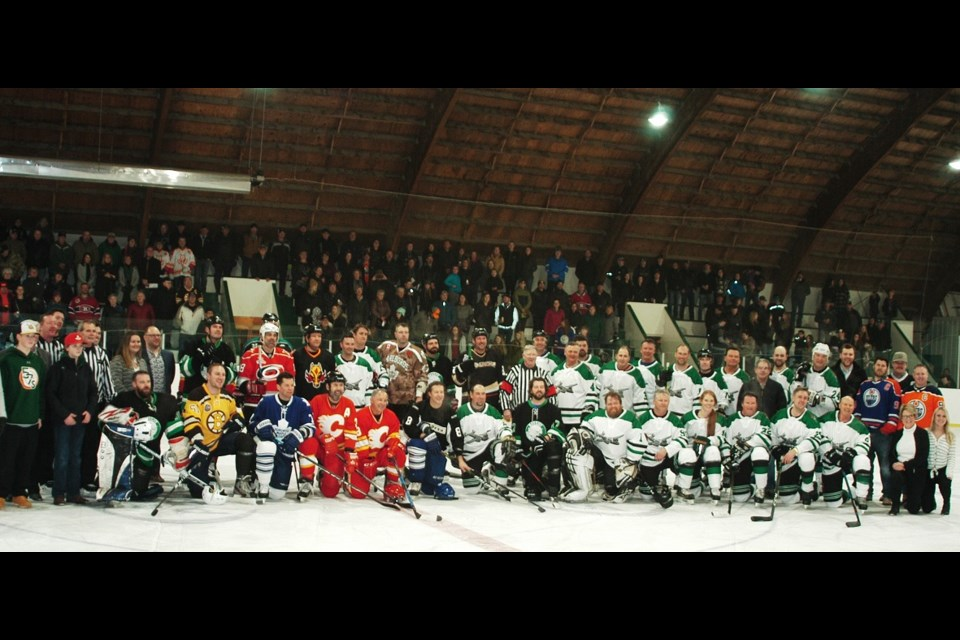 Teams, coaches, and staff gather for a group shot at center ice.