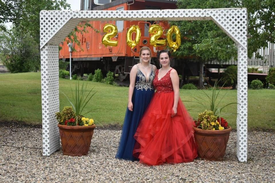 Dressed in formal wear, KCI graduates Brooke Schwartz, left, and Samantha Chernoff were photographed under a 2020 banner at Trackside Garden on June 29.