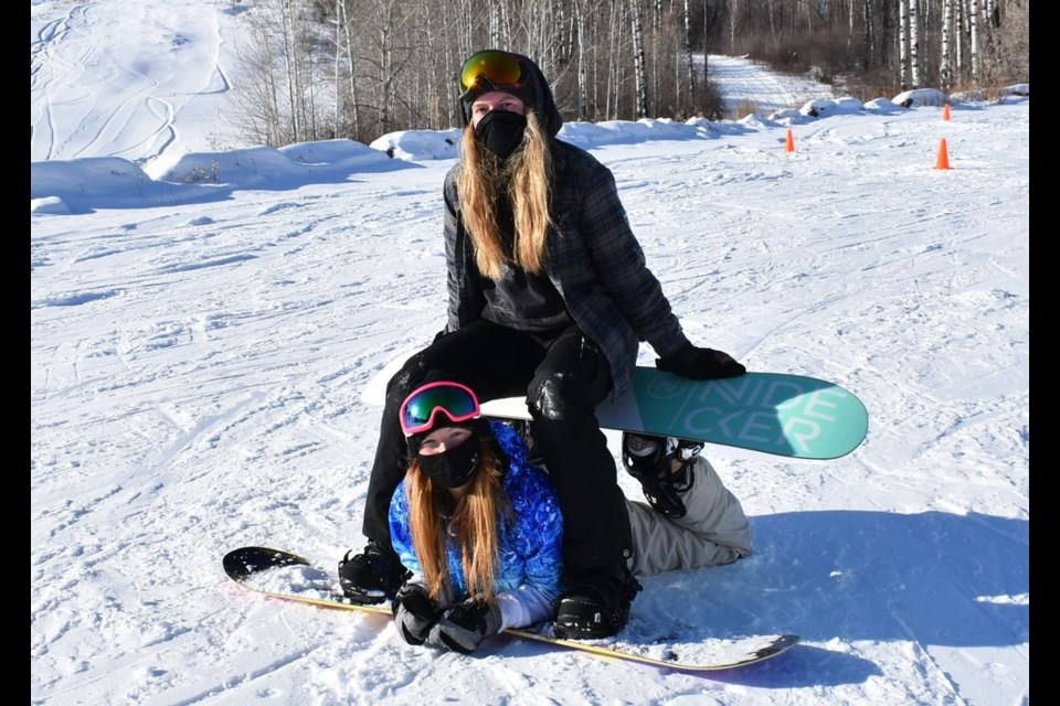 Staff members at the Duck Mountain Ski Area, Shaelyn David and Michaela MacKenzie are seen here modeling some of their Tik Tok inspired snowboarding moves.