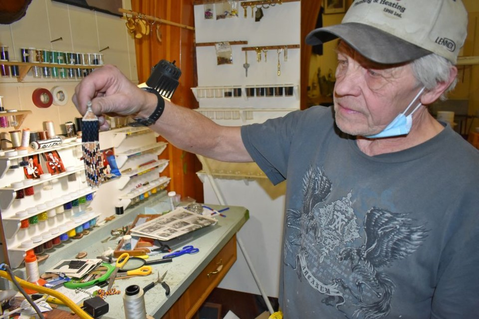First Earrings Allan Bennett holds up the very first pair of beaded earrings he made in his studio in Kamsack.