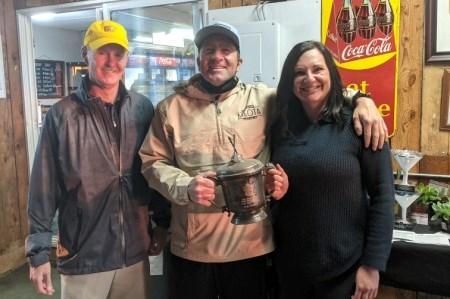 Meota Golf Course Swingers' Open sponsor Shandon Reichert (left) presenting the Swinger's Cup to Kyle McNamara and Jade Johnson.