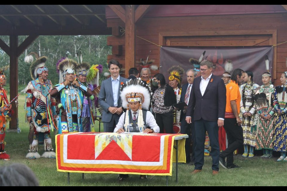 Chief Cadmus Delorme (seated), Prime Minister Justin Trudeau (L) and Saskatchewan Premier Scott Moe (R) gathered at Cowessess First Nation to sign the agreement transferring power over child services back to the Indigenous council.