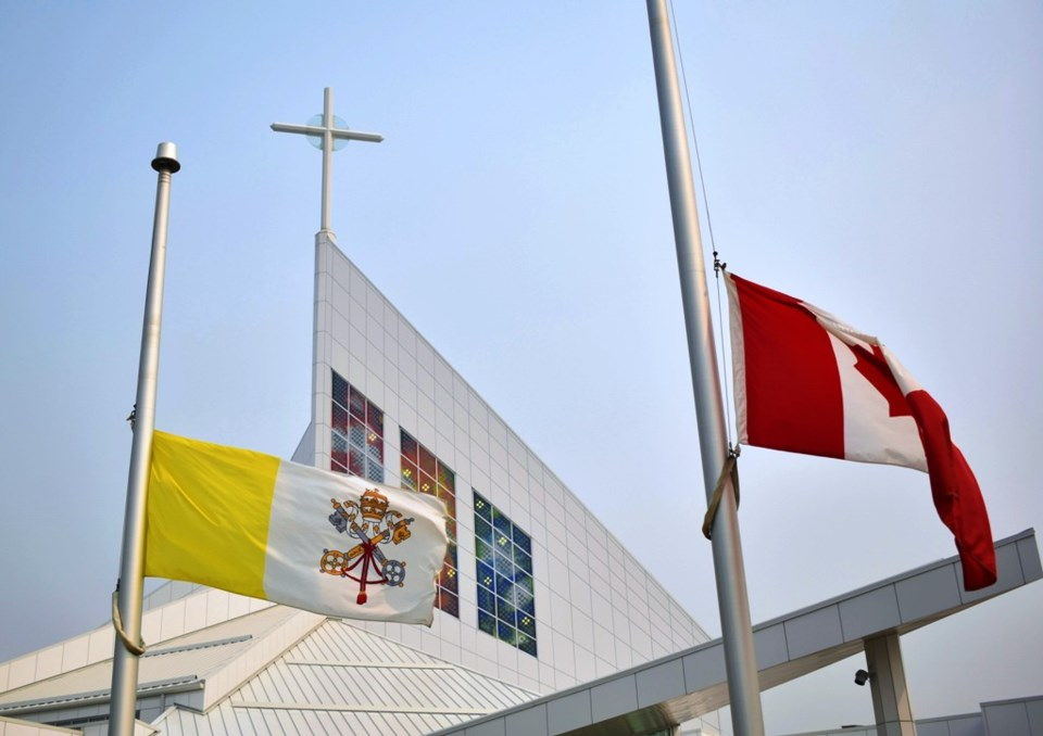 The flags of the Vatican, left, and Canada at the Roman Catholic Cathedral of the Holy Family