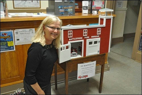 Curator of the Fred Light Museum Bernie Leslie with this year's raffle project, a dollhouse version of the 1905 replica fire hall that makes up part of the museum complex. Made and donated by the museum board chair Floyd Anderson, the dollhouse draw will be made in December.