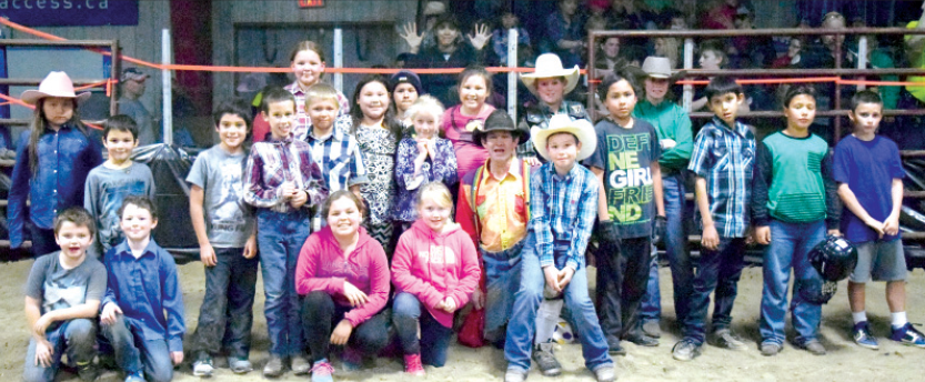 This is a photograph of the group of youngsters who participated in the wild pony races held during Saturday's rodeo. They were photographed with the bull fighter, who while dressed in colourful garb, is the man who attempts to take the bull's attention away from the rider.