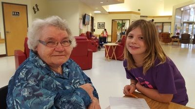Tess Covlin, right, enjoyed listening to Rosie Yurfiw's story on November 22 when the Preeceville School Grade 3 class visited with the long term care residents in Preeceville.