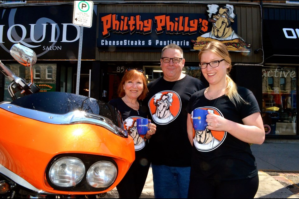 Lina and Mark Russell with their daughter and business partner Alysse Osbourne outside Philthy Philly's their new restaurant on Macdonell.  Troy Bridgeman for GuelphToday.com