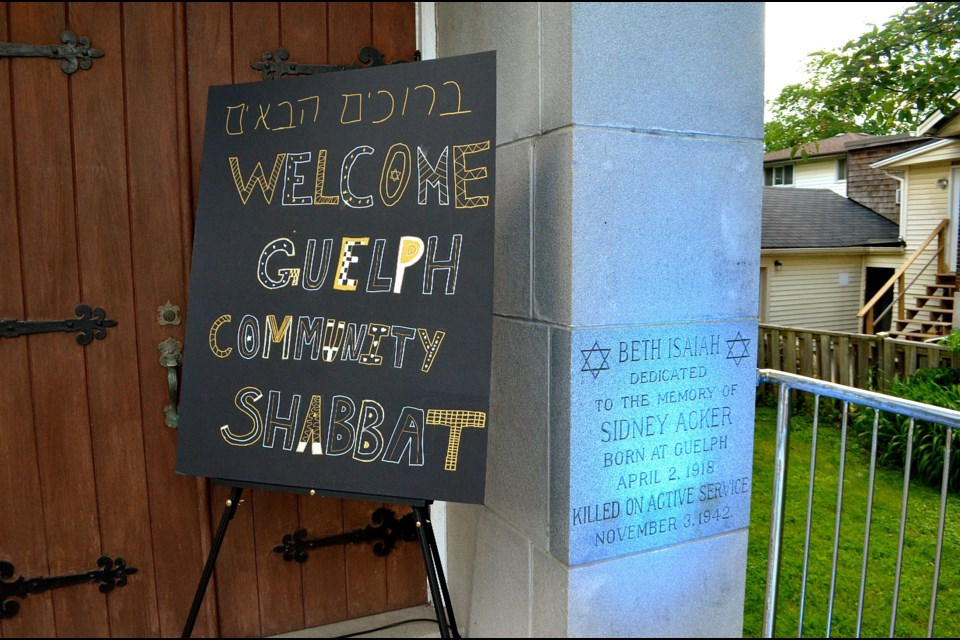 A sign at the entrance to Beth Isaiah Synagogue welcomes people to a special Shabbat Dinner and beside it is a dedication stone for Sidney Acker who was killed in action during the Second World War.  Troy Bridgeman for GuelphToday.com