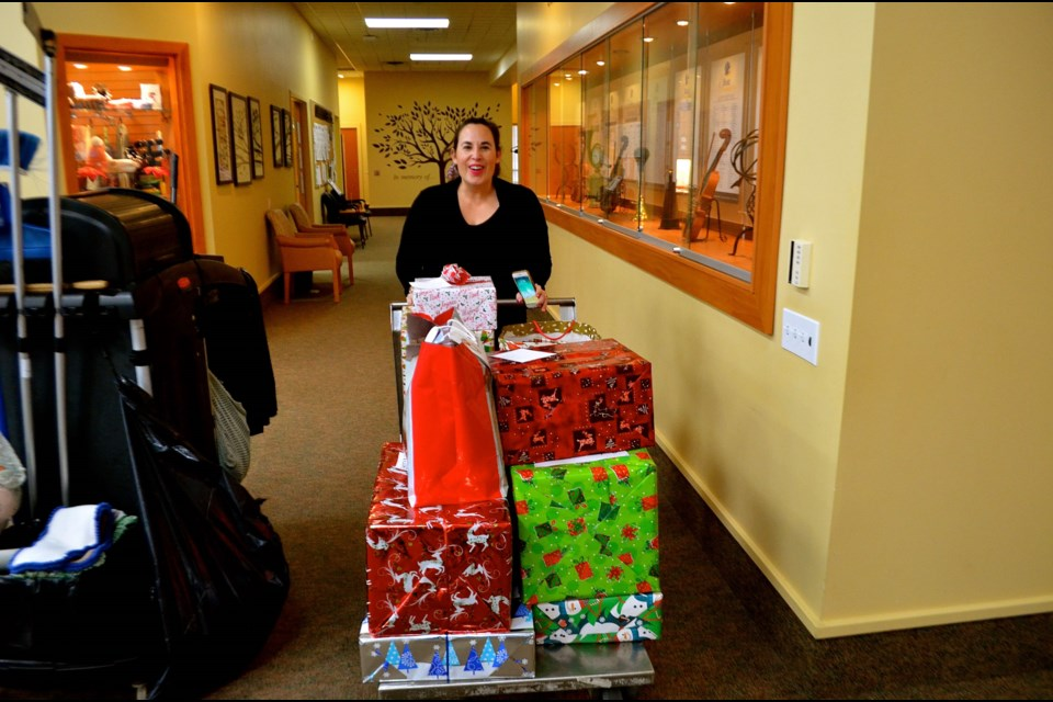Kyla Rowntree moves wrapped gifts for delivery at the Elliott Community. Troy Bridgeman for GuelphToday.com